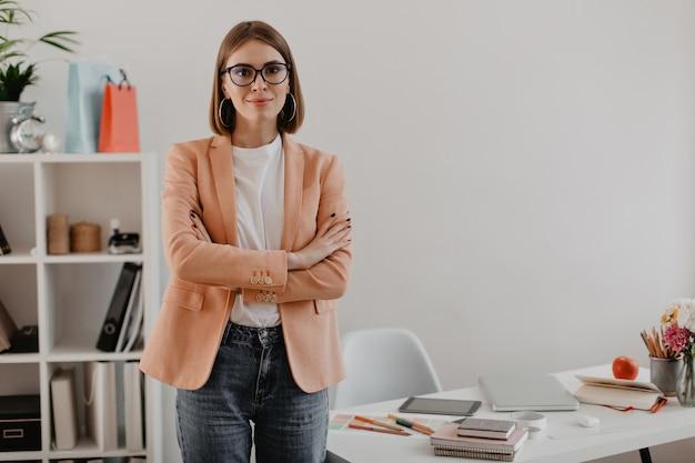 Vrouwelijke ondernemer in uitstekende stemming met haar armen gekruist tegen heldere werkplek.