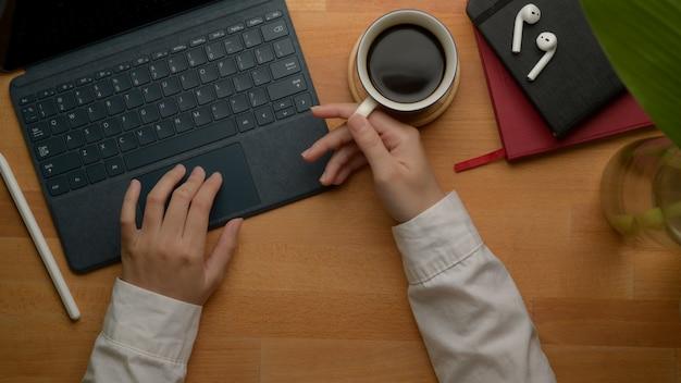 Vrouwelijke ondernemer links gebruikend digitale tablet en rechtse holdingskoffiekop