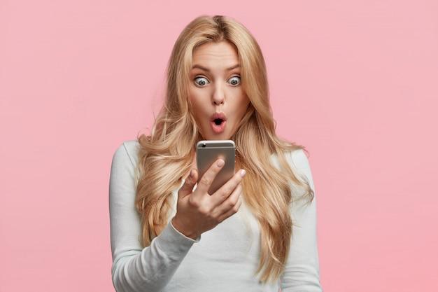 Vrouwelijke ondernemer of zakenvrouw die teleurgesteld is met nieuws van collega, leest bericht op smartphone, geschokt om verantwoordelijkheid te ontvangen, bereidt moeilijk project voor op de vergadering van morgen