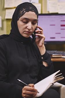 Vrouwelijke ondernemer uit het midden-oosten. drukke arabische zakenvrouw. vrouw in traditionele arabische kleding hijab of abaya die op pc werkt
