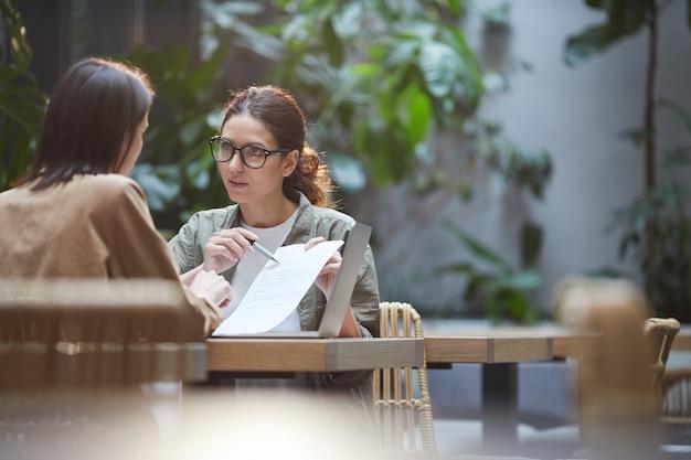Vrouwelijke ondernemers bespreken business project in cafe