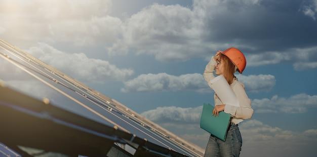 Vrouwelijke ondernemers bezig met het controleren van apparatuur op de tabletcontrolelijst van de zonne-energiecentrale