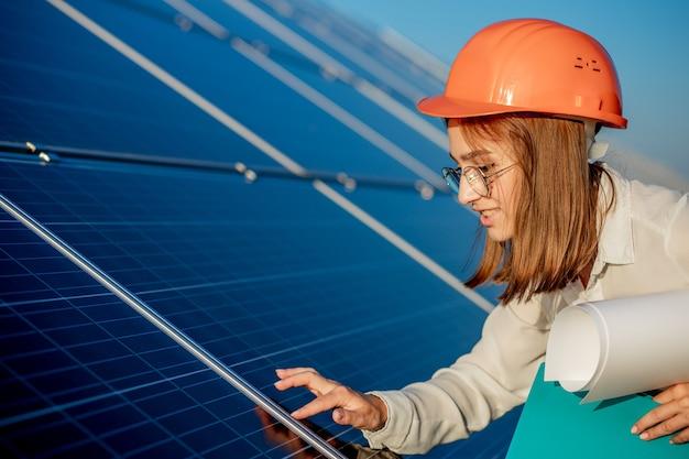 Vrouwelijke ondernemers bezig met het controleren van apparatuur op zonne-energiecentrale met tablet-checklist, vrouw bezig met buiten op zonne-energiecentrale.