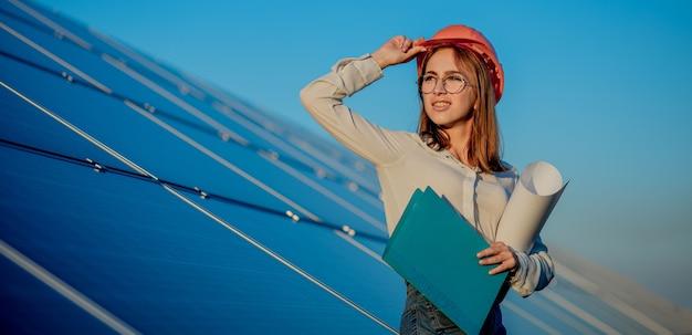 Vrouwelijke ondernemers bezig met het controleren van apparatuur op zonne-energiecentrale met tabletchecklist