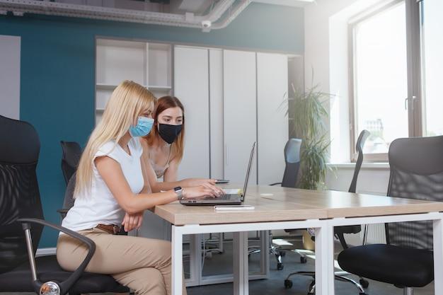 Vrouwelijke ondernemers die tijdens het werk beschermende gezichtsmaskers dragen