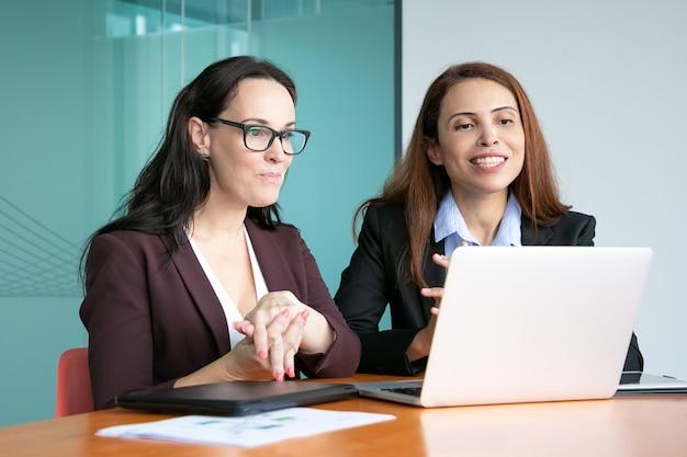 Vrouwelijke ondernemers hebben video praten met partners, zitten op open laptop, kijken naar display en glimlachen