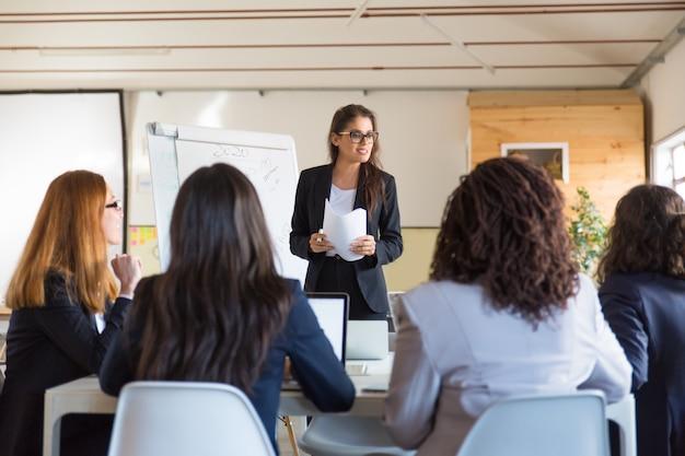 Vrouwelijke ondernemers kijken naar spreker met papieren