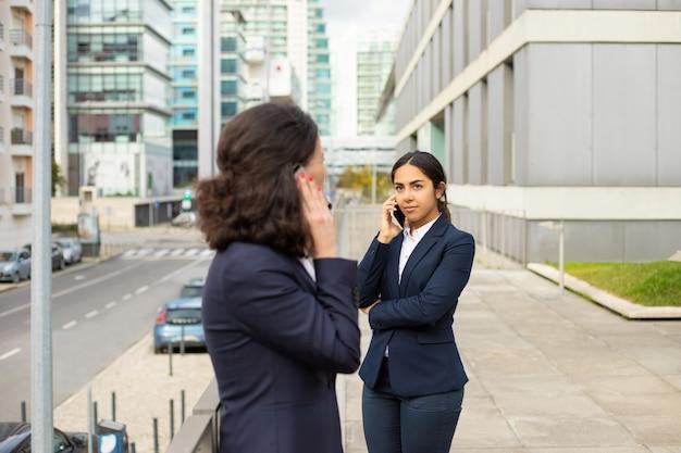 Vrouwelijke ondernemers praten door smartphones op straat