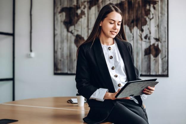 Vrouwelijke ondernemers werken op een tablet verspreidt zich op een bureau, op kantoor