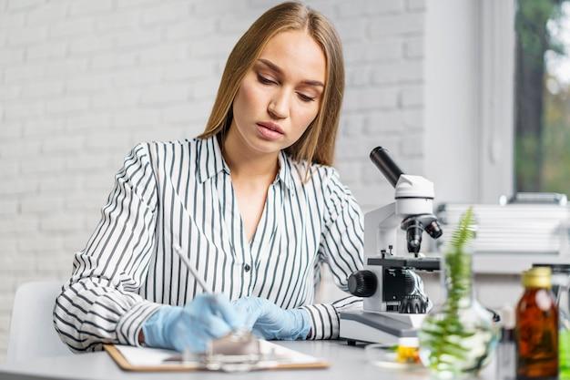 Vrouwelijke onderzoeker bij haar bureau met microscoop en klembord