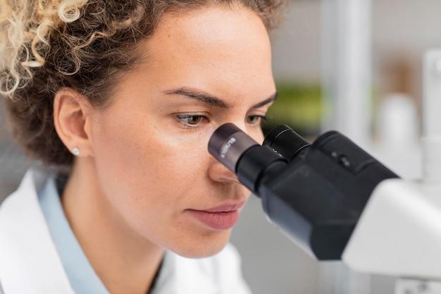 Vrouwelijke onderzoeker die in het laboratorium door microscoop kijkt