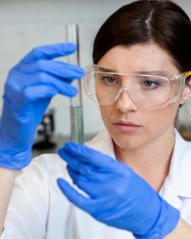 Vrouwelijke onderzoeker met reageerbuis en veiligheidsbril