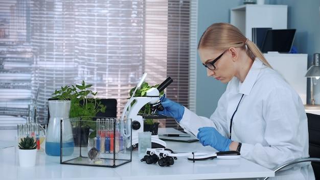 Vrouwelijke onderzoekswetenschapper die organisch materiaal met pincet op dia zet.