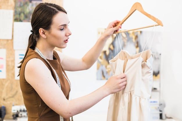 Vrouwelijke ontwerper die aan nieuw kledingontwerp werkt