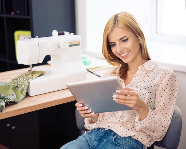 Vrouwelijke ontwerper die tabletcomputer gebruikt
