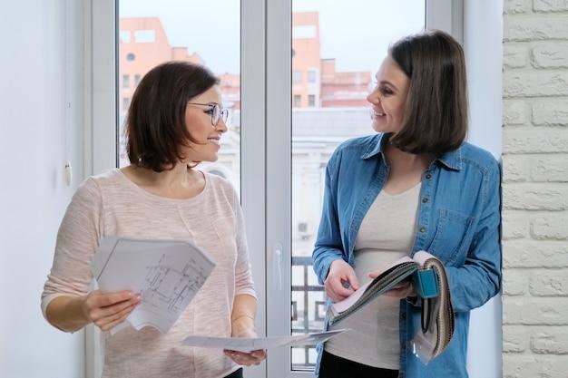 Vrouwelijke ontwerper en klant die met stofmonsters werken. stoffen selecteren en gordijnen ontwerpen, vrouwtjes bij raam met schets en materialen