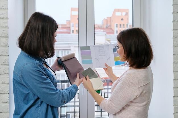 Vrouwelijke ontwerper en klant die met stofstalen werken. stoffen selecteren en gordijnen ontwerpen