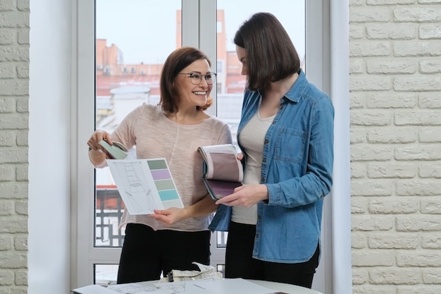 Vrouwelijke ontwerper en opdrachtgever werken met stofstalen