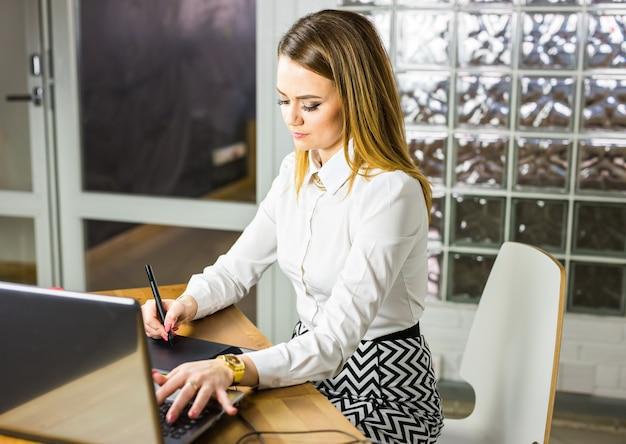Vrouwelijke ontwerper in bureau die met digitale grafische tablet en laptop werken. fotografie retoucher zitten aan de balie.