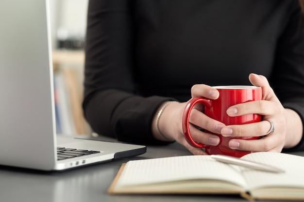 Vrouwelijke ontwerper in kantoor 's ochtends thee of koffie drinken. koffiepauze tijdens een zware werkdag. meisje met kopje warme drank.