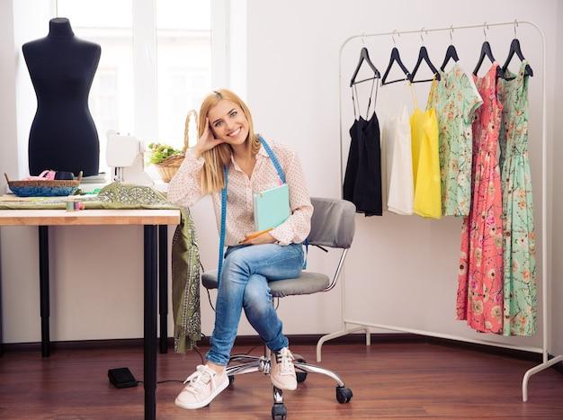 Vrouwelijke ontwerper in werkplaats met notitieboekje