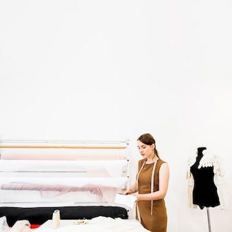 Vrouwelijke ontwerper scherpe stof met schaar