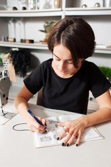 Vrouwelijke ontwerper tekenen van schetsen van kledingzakken in notitieblok
