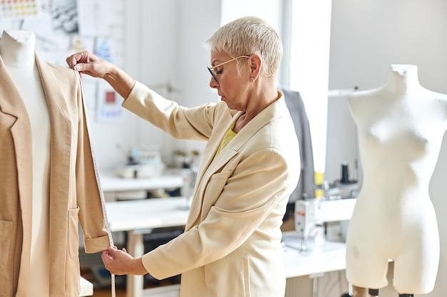Vrouwelijke ontwerper van middelbare leeftijd meet de mouw van een elegant jasje in een lichte werkplaats