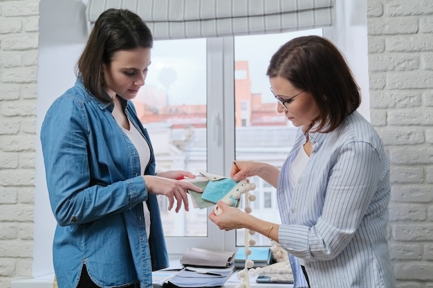 Vrouwelijke ontwerpers die stoffen en accessoires voor gordijnen kiezen met een huisproject