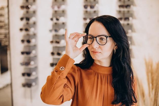 Vrouwelijke oogarts demonstrerende bril in opticien shop
