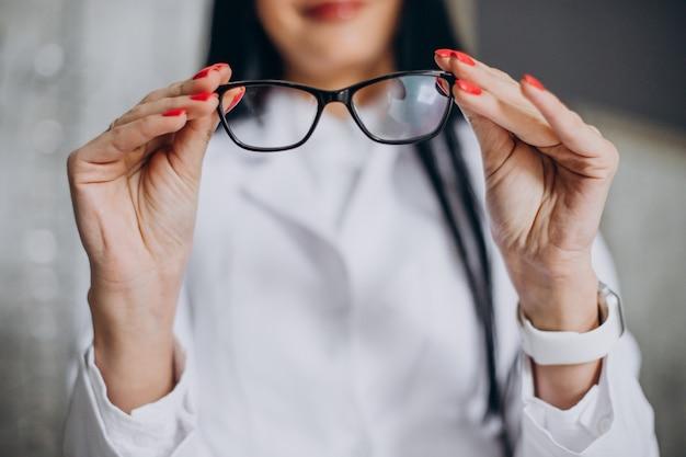 Vrouwelijke oogarts die een bril demonstreert in de opticienwinkel