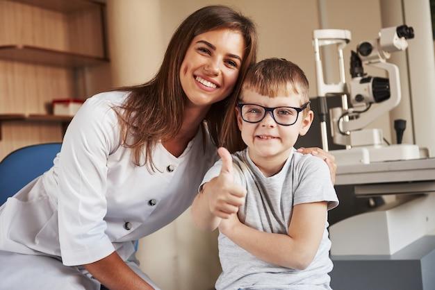 Vrouwelijke oogarts zit met het kind na het doen van de visie-test.