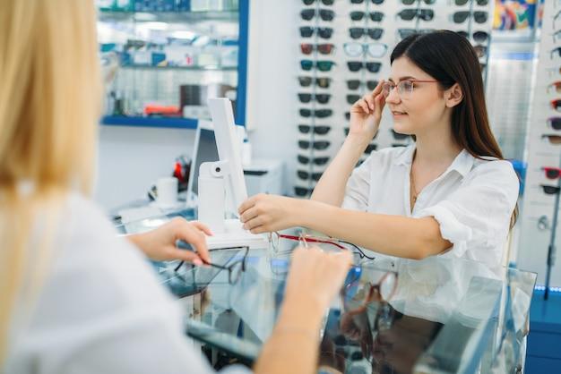 Vrouwelijke opticien en consument kiest brilmontuur