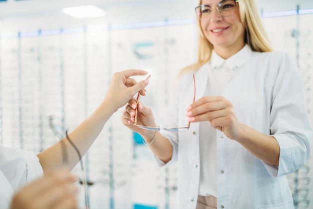 Vrouwelijke opticien en klant schudt glazen