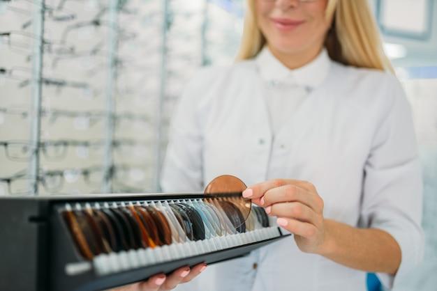 Vrouwelijke opticien houdt doos met lenzen van verschillende kleuren, showcase met bril in optica winkel op ruimte. zonnebrillenkeuze, oogzorg, bescherming tegen zonlichtconcept
