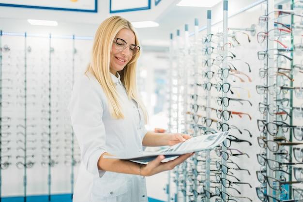 Vrouwelijke opticien met glazen catalogus in handen