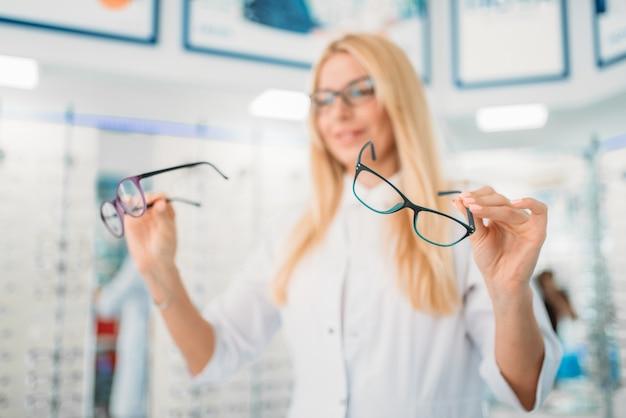Vrouwelijke opticien tegen showcase met bril