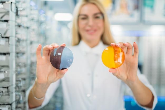 Vrouwelijke opticien toont lenzen van verschillende kleuren, showcase met bril in optica winkel
