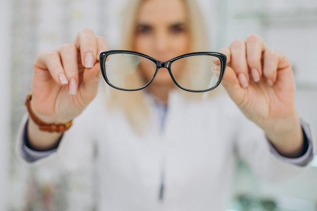 Vrouwelijke opticien werken bij optische winkel