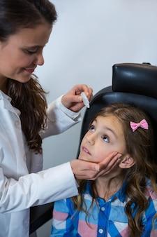 Vrouwelijke optometrist die druppels in de ogen van jonge patiënten zet