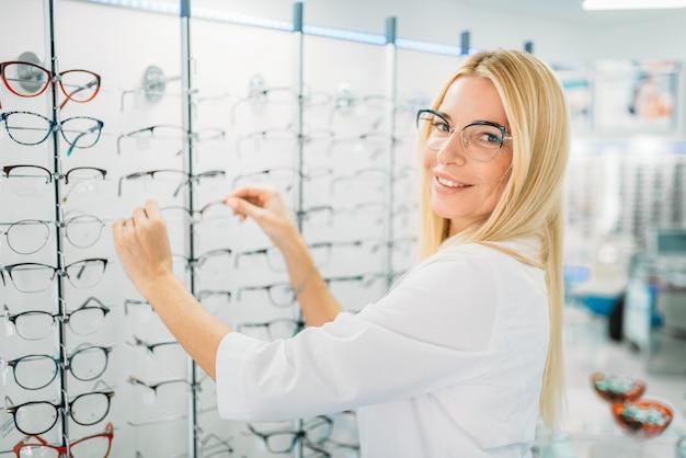 Vrouwelijke optometrist toont bril in optica winkel. selectie van brillen met professionele opticien, optometrie