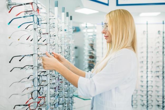 Vrouwelijke optometrist toont bril in optica winkel