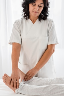 Vrouwelijke osteopaat die de benen van een patiënt behandelt in het ziekenhuis