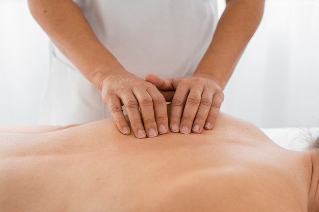 Vrouwelijke osteopaat die een jonge vrouw behandelt door haar te masseren