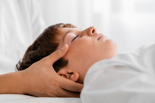 Vrouwelijke osteopaat die een kind behandelt door zijn hoofd te masseren