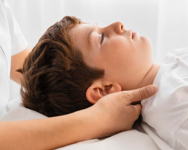 Vrouwelijke osteopaat die een kind in het ziekenhuis behandelt