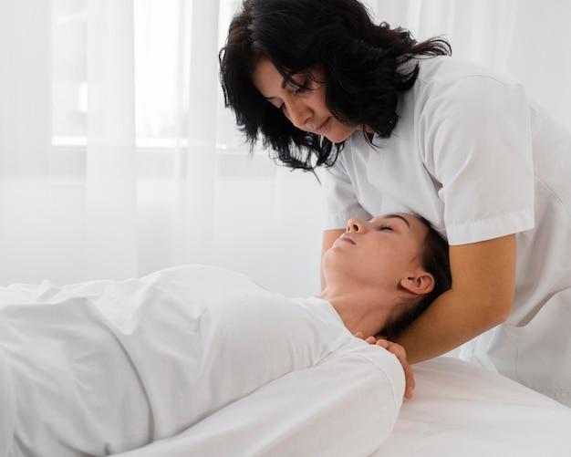 Vrouwelijke osteopaat die een meisje behandelt in het ziekenhuis