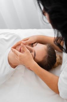 Vrouwelijke osteopaat die een patiënt behandelt