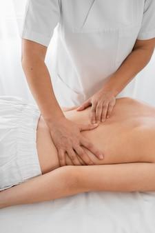 Vrouwelijke osteopaat die een shirtless vrouw binnenshuis behandelt