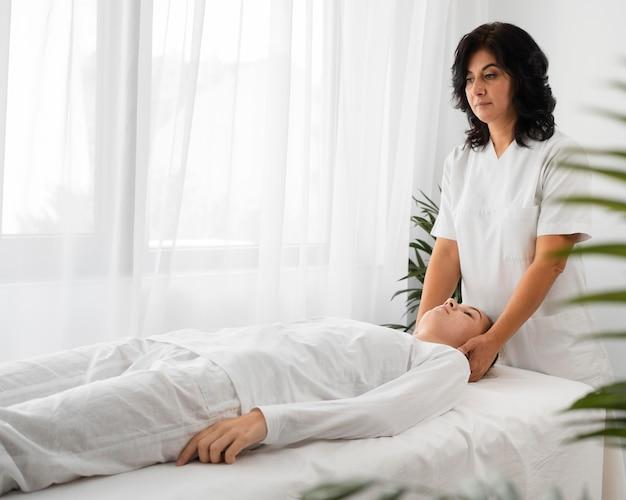Vrouwelijke osteopaat die een vrouwelijke patiënt behandelt door haar gezicht te masseren